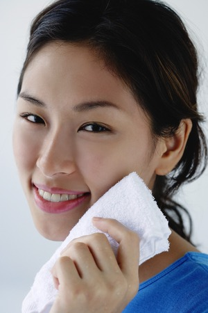 face cloth: A young woman smiles at the camera as she washes her face