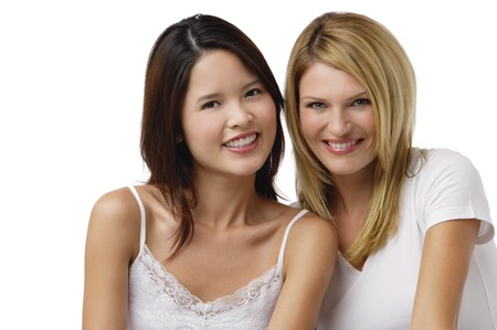 Two young woman wearing white shirts and smiling at camera