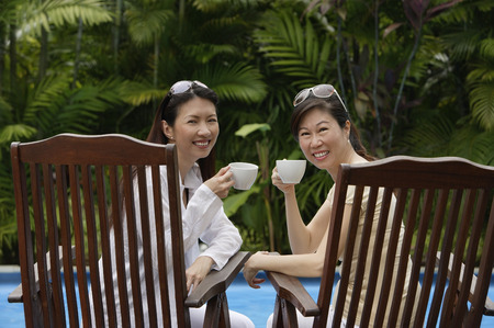 Two women sitting side by side outdoors, holding cups, turning to look at camera