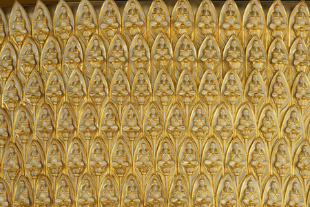 Structure covered with golden Buddhas sitting in lotus Imagens