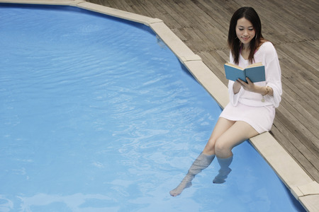 poolside: Young woman reading poolside