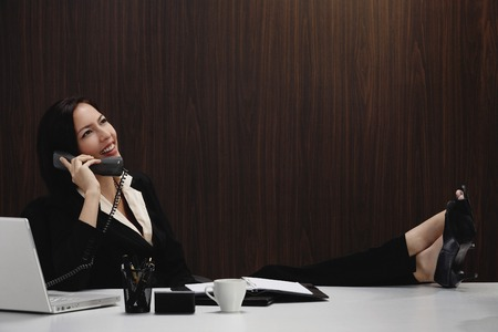 A woman talks on the phone while she is at her desk