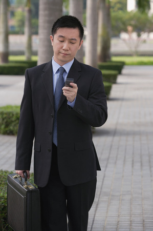 three persons only: Businessman holding mobile phone LANG_EVOIMAGES