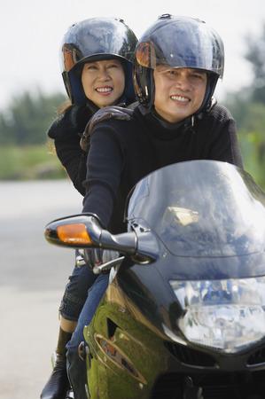 transportation: Man and woman riding motorcycle, wearing helmets, looking at camera