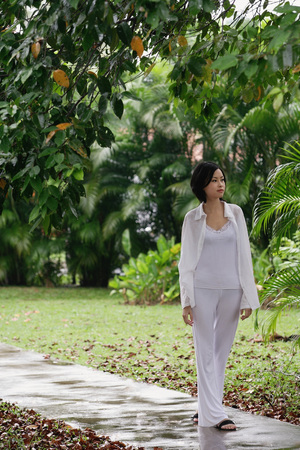 only 1 person: A woman strolls down a path in a garden