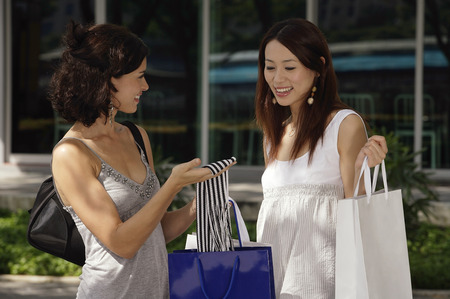 Women with shopping bags having a conversation