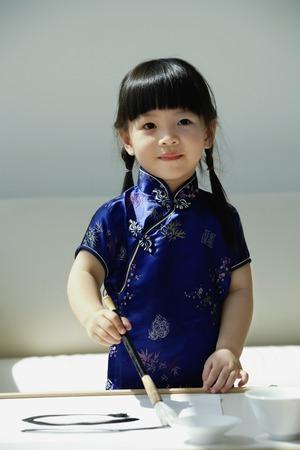 Ein kleines Mädchen in blauer Seide cheongsam Schrift der chinesischen Kalligraphie