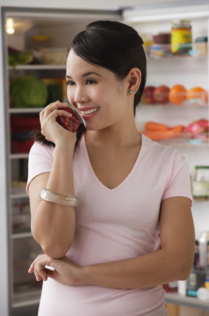 Young woman holding apple and smiling Stock Photo