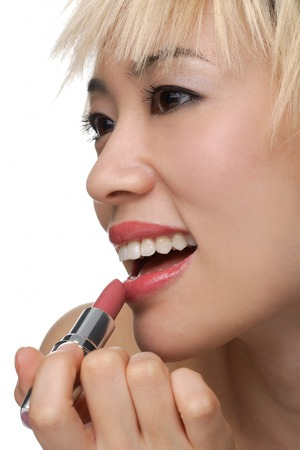 A young woman applies lipstick Stock Photo