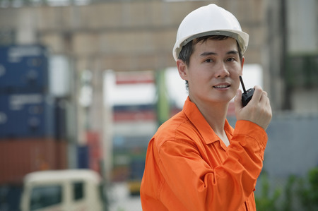 Construction worker talking on walkie talkie Stock Photo