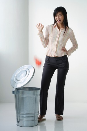 A woman throws something in the rubbish bin LANG_EVOIMAGES