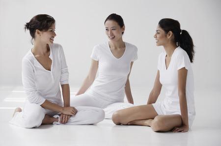 three women of mixed race sitting on floor talking
