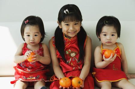 Girls with mandarin oranges sitting on sofa