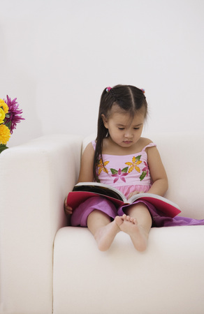 3 4 years: A young girl sitting on the couch with a book