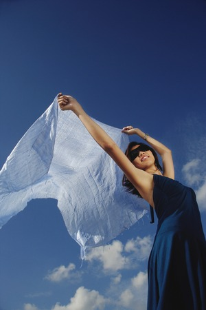 A young woman dances in the wind with a veil Imagens
