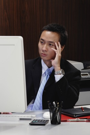 A man concentrates as he works at his desk
