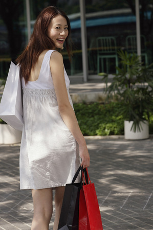 Woman with shopping bags, smiling over shoulder at camera Stock Photo