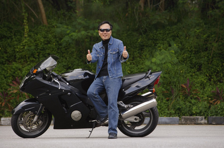 Man sitting on motorcycle, giving thumbs up Imagens