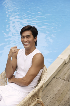 poolside: Young man sitting poolside LANG_EVOIMAGES