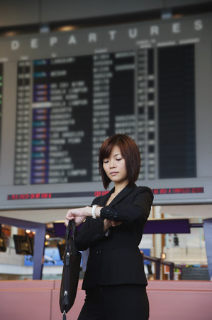 only 1 person: Young woman waiting at the airport LANG_EVOIMAGES