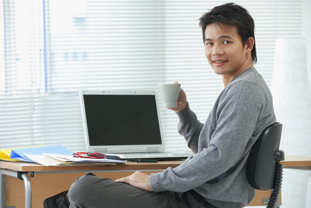 Man with cup relaxing at desk and looking at camera