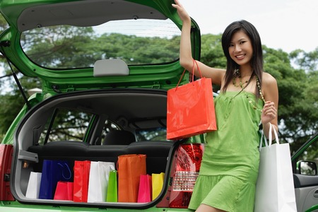happy asian people: A young woman puts her shopping in the back of a car LANG_EVOIMAGES