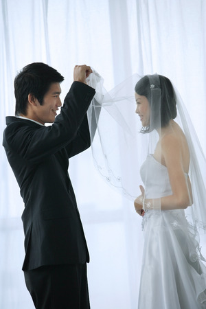 commit: The groom lifts the brides veil to kiss her LANG_EVOIMAGES