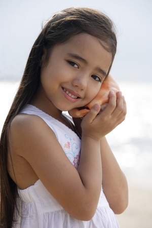 Young girl on beach holding conk shell to her ear, smiling