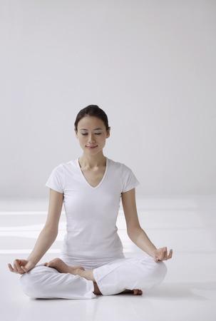 Woman sitting cross legged on floor, meditating, eyes closed
