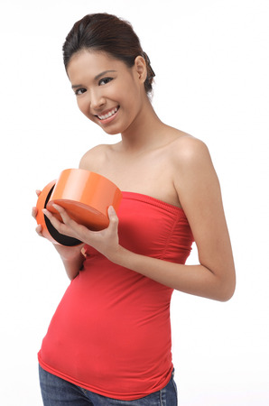 Young woman smiling at camera, holding box LANG_EVOIMAGES