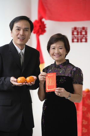 wedding customs: A couple look at the camera as they hold two oranges and a red envelope