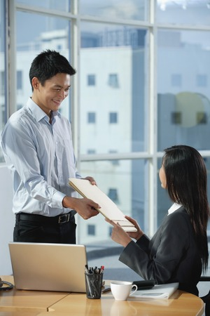 Two colleagues smile at each other as they exchange documents 写真素材