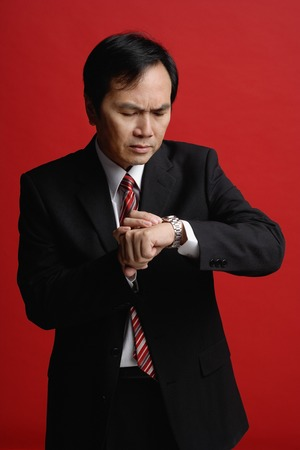only 1 person: A businessman checks his watch for the time LANG_EVOIMAGES
