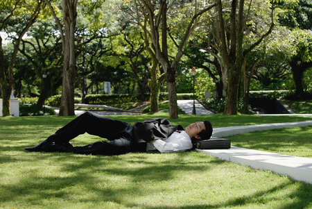 break from work: A man lies down and has a rest in the park