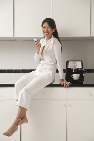 Woman sitting on counter in kitchen next to a cappuccino / coffee machine, sending / receiving text message 免版税图像