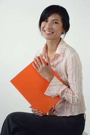 A woman smiles at the camera as she holds an orange folder