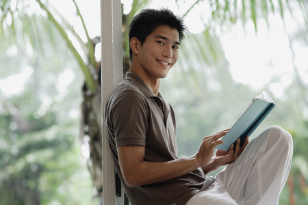 A man smiles at the camera as he reads a book