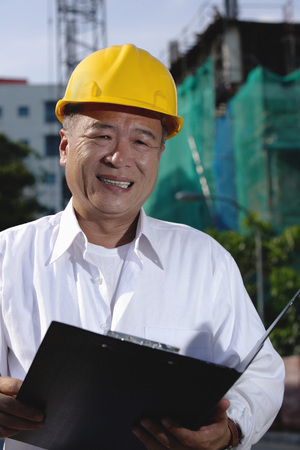 A man with a yellow helmet smiles at the camera, holding file