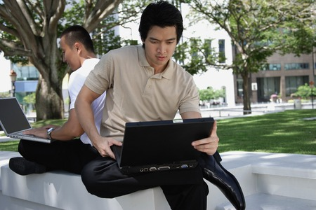 Two men use their laptops in the park