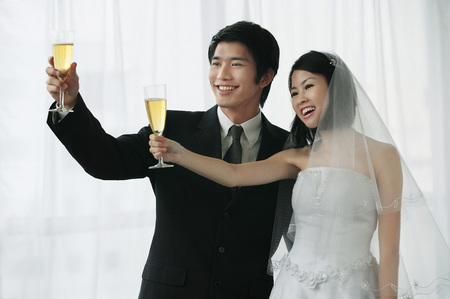commit: A newlywed couple hold out their champagne glasses for a toast LANG_EVOIMAGES