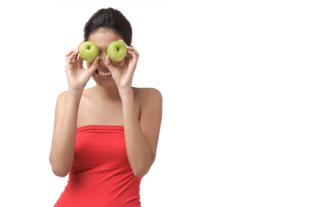 Young woman holding two apples over eyes