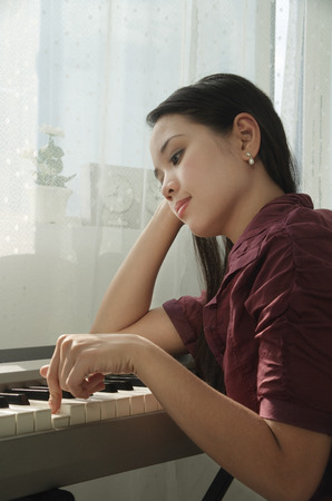 Young woman playing keyboard Stock Photo