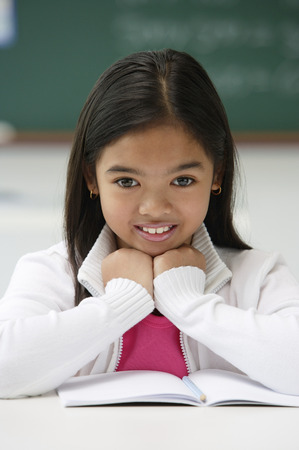 Girl sitting at school desk and smiling at camera Stock Photo