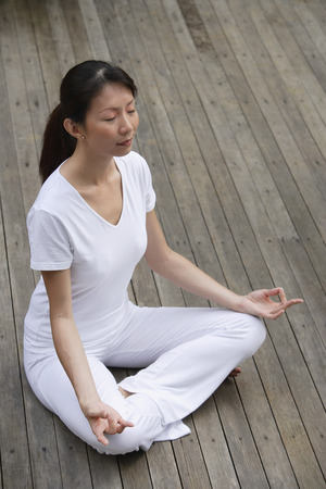 affluence: Woman meditating on porch, eyes closed, in yoga OM posture.