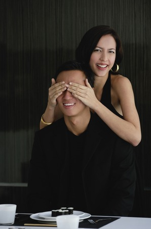 dinner wear: A woman covers her boyfriends eyes as she prepares to surprise him with dinner LANG_EVOIMAGES