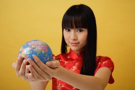 cradling: Young woman wearing red cheongsam and holding globe in the palm of her hands LANG_EVOIMAGES