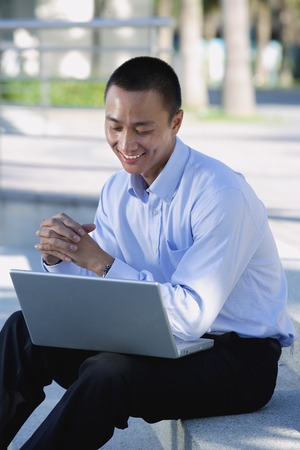 professionally: A man smiles as he uses his laptop outdoors