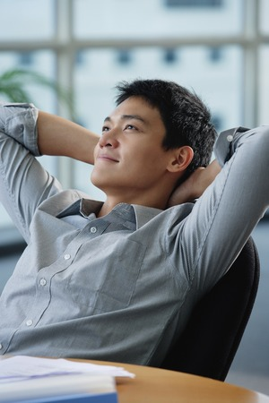 professionally: A man relaxes at his desk LANG_EVOIMAGES