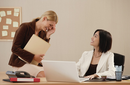 noteboard: Two female colleagues smile and laugh together at work