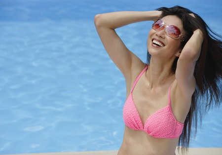 homeownership: Woman in pink bikini, sitting by swimming pool, hands in hair, smiling LANG_EVOIMAGES